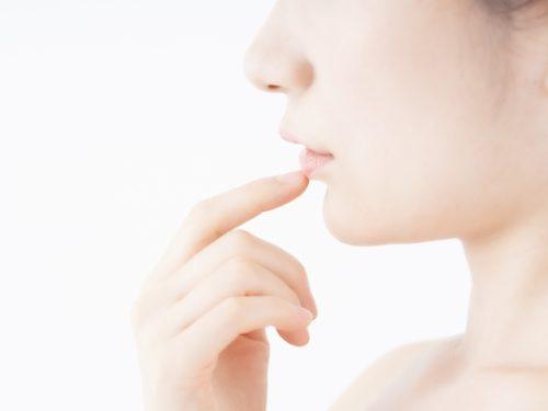 唇をさわる女性